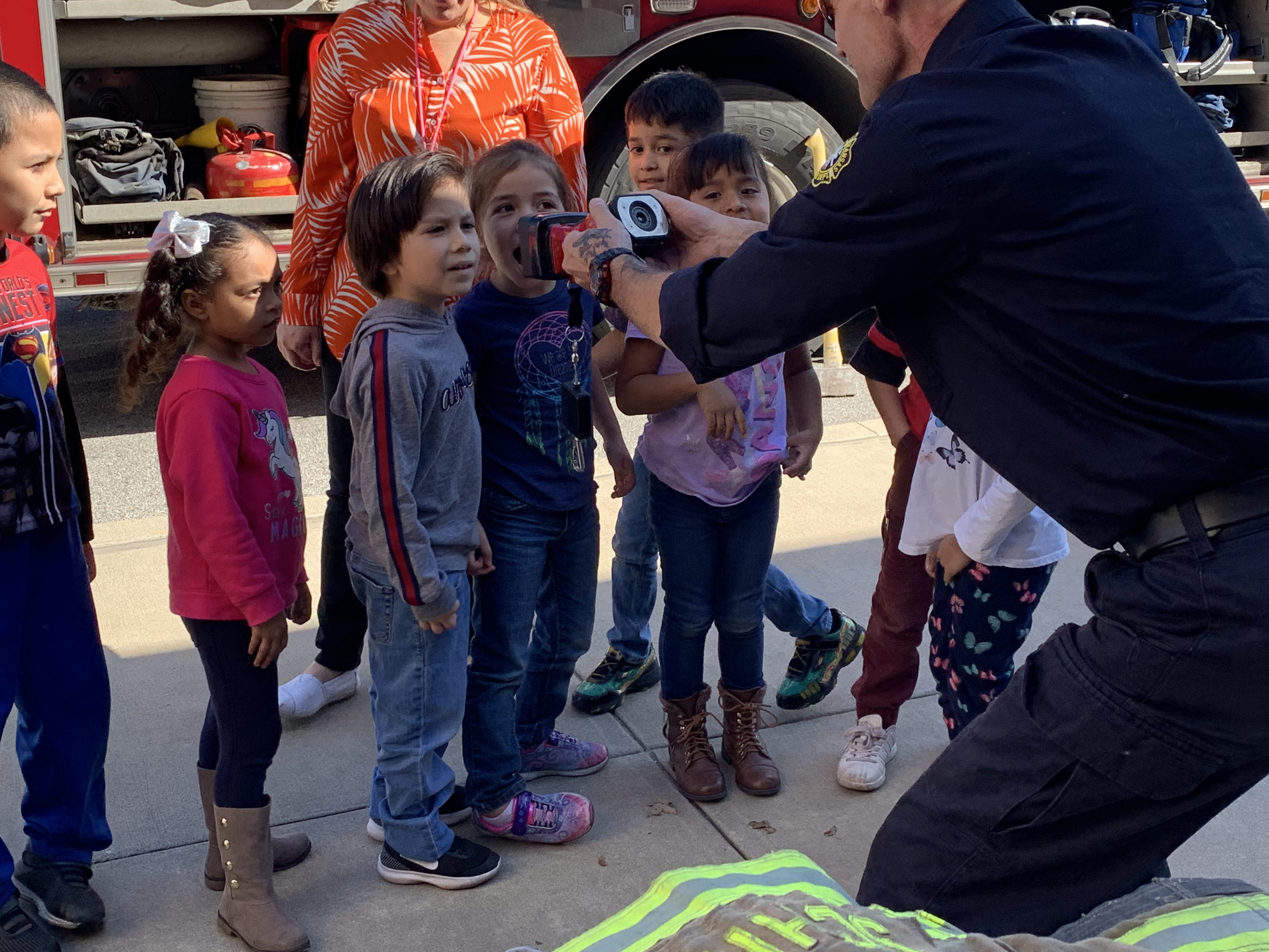 Students look at tools that firefighters use to see through smoke and darkness.