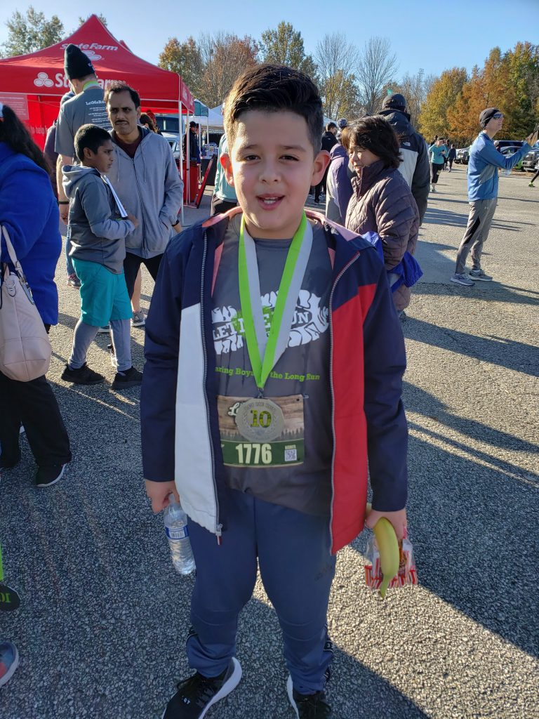Student with medal after finishing the Let Me Run 5K
