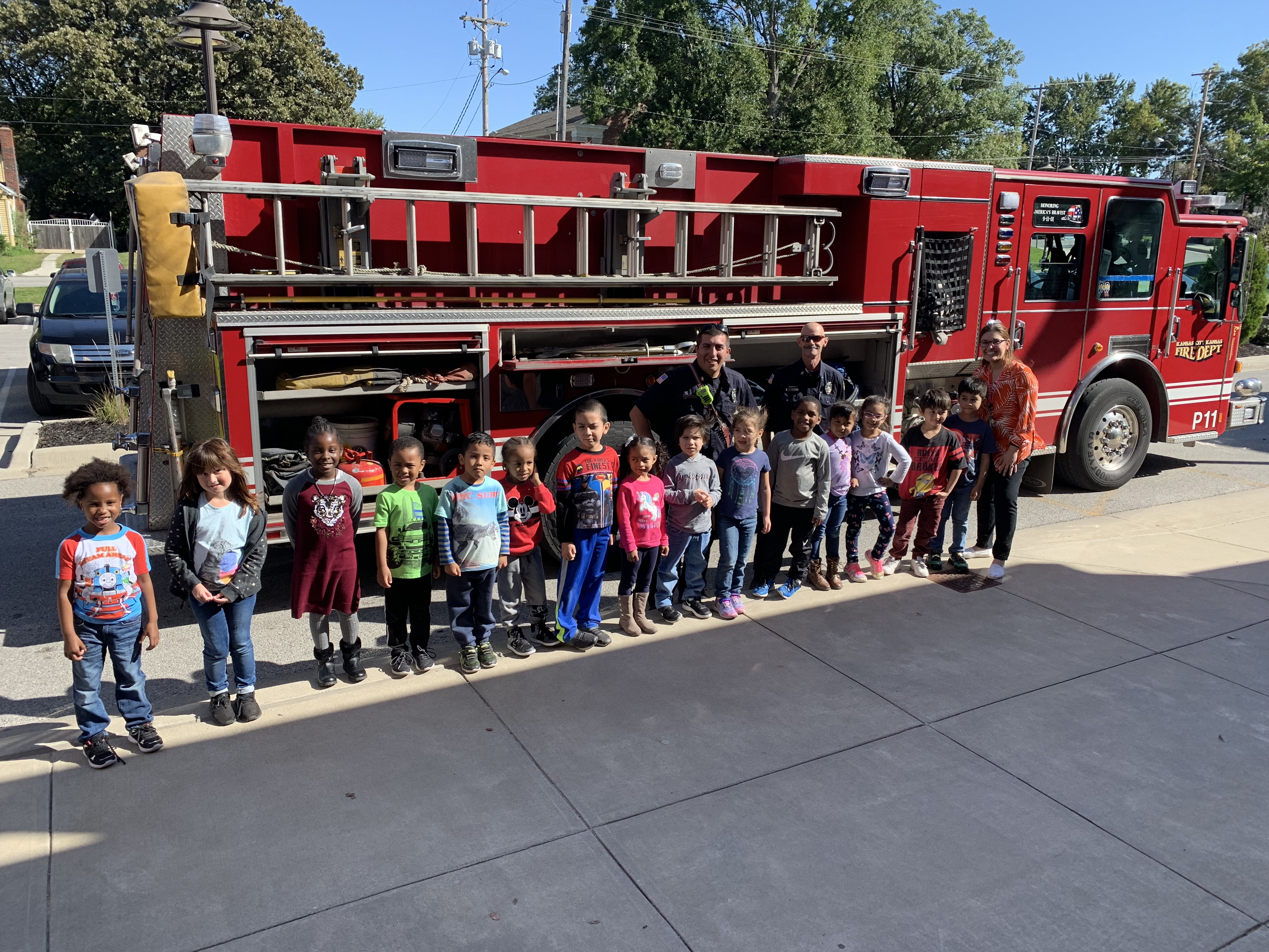 Ms. Merlos's kindergarten class poses in front of fire engine with two KCK firefighters.